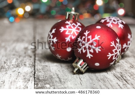 close on red christmas balls with snowflake on  a plank with colorful lights background
