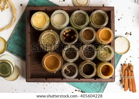 Close photo of different spices and herbs in small glass jars. Anise, allspice, cloves, carry, pepper, chilly, turmeric  on blue painted wooden board. Food, cuisine ingredients photography. - stock photo