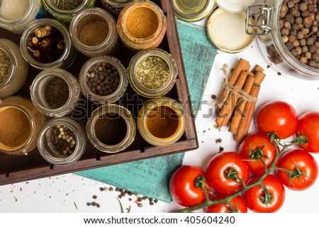 Close photo of spices and herbs, small glass jars. Anise, allspice, cloves, carry, pepper, chilly, turmeric, blue painted wooden board. Cherry tomatoes branch. Food, cuisine ingredients photography. - stock photo