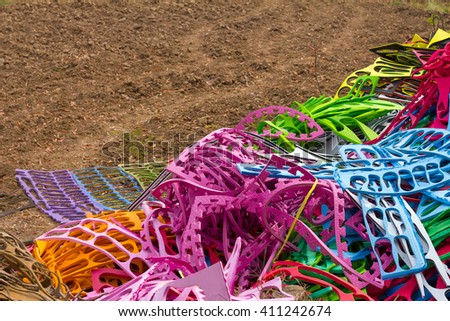 Close-piece molded foam rubber shoes, which are abundant colorful pile on the ground. - stock photo
