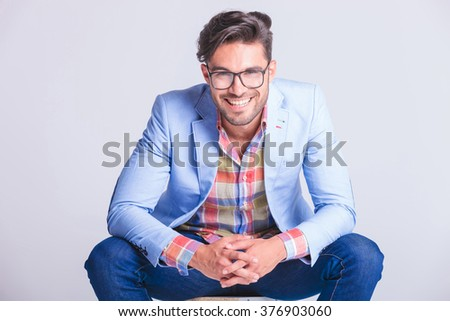 close portrait attractive man posing seated with legs spread open and hands touching, while smiling at the camera in studio background