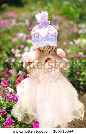 Close portrait little child playing in flowers field