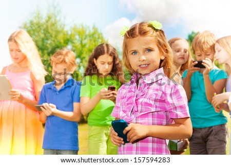 Close portrait Little girl with standing and texting with the phone standing in the park with group of friends