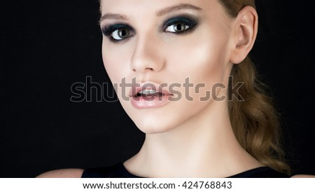 Close portrait of a beautiful young blonde with a tail black background