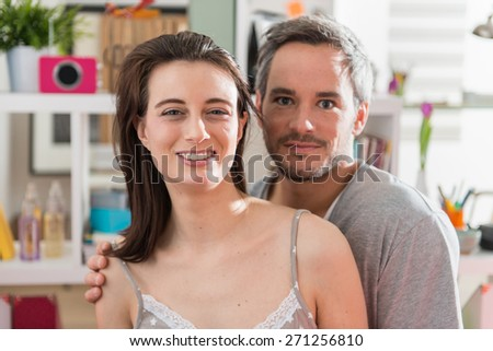 close portrait of a cheerful couple looking at the camera at home, their interior is modern and bright - stock photo