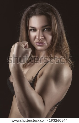Close portrait of a girl bodybuilder with tight muscles.