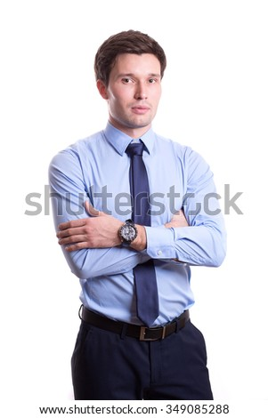close portrait of a handsome young man in office clothes in a blue shirt trousers tie stands isolated on a white background