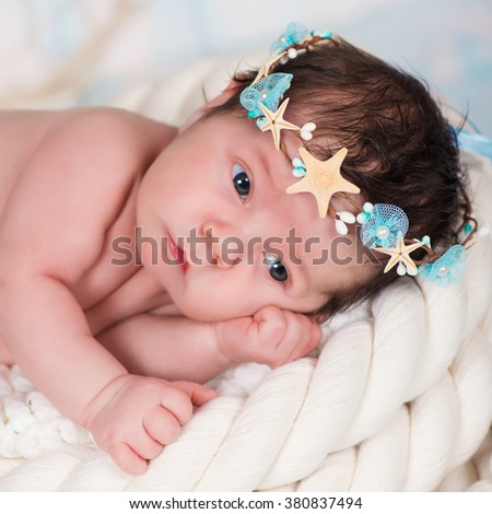 Close portrait of a sleeping newborn girl in the maritime hoop of starfish and pearls - stock photo