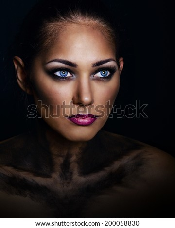 Close portrait of a young attractive girl with a make-up of an animal shot in a studio - stock photo
