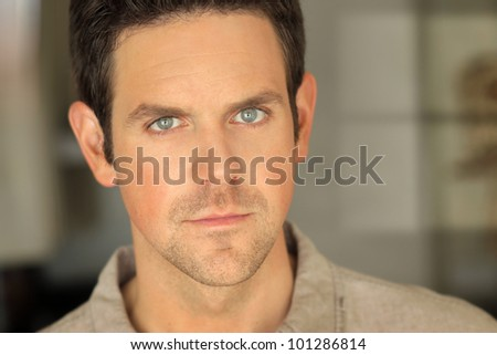 Close portrait of a young man's face with serious pensive expression - stock photo
