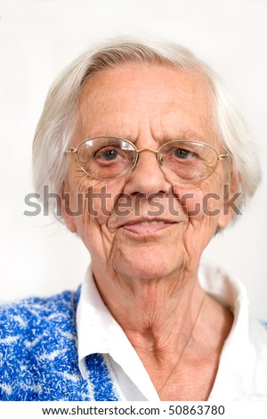 Close portrait of an elderly woman wearing glasses and a blue knitted sweater.