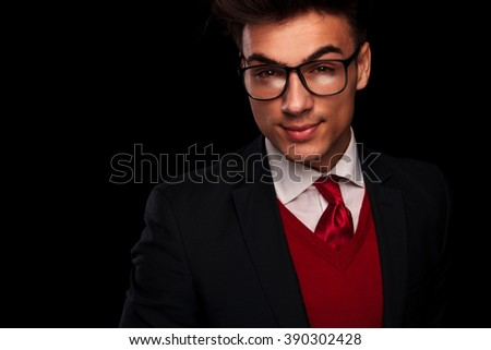 close portrait of attractive young man in suit, wearing tie and glasses, looking at the camera in dark studio background