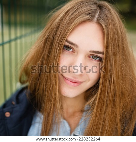 Close portrait of beautiful girl with long hair , beautiful smile and a pleasant look in autumn jacket on background mini football playground in autumn
