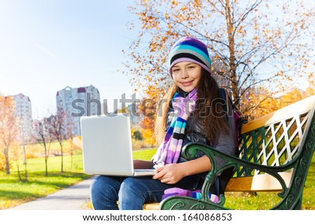 Close portrait of beautiful school girl sitting on the bench in park with laptop top on sunny autumn day