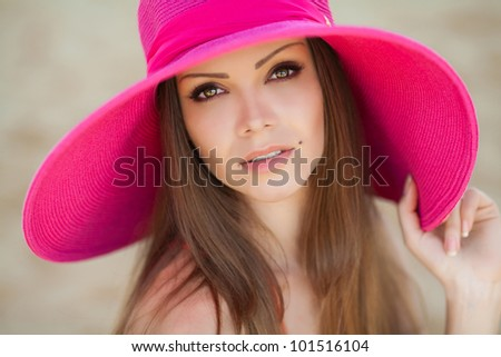 close portrait of beautiful young woman in bright summer hat sitting on the beach - stock photo