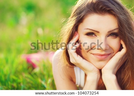 Close portrait of beautiful young woman on green grass in the summer outdoors - stock photo