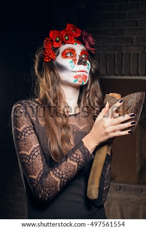 Close portrait of female daemon with sugar skull makeup and axe in hands. Face painting art.
