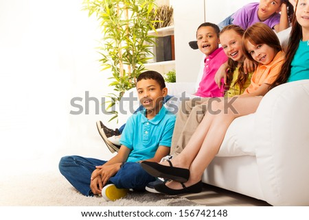 Close portrait of group of kids, boys and girls sitting together in living room