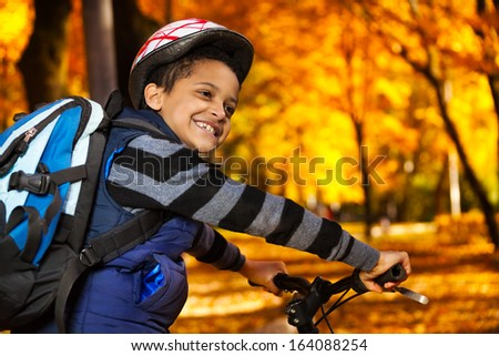 Close portrait of happy laughing 8 years old boy with backpack riding a bike in the autumn park leaning on bicycle stern turning back - stock photo