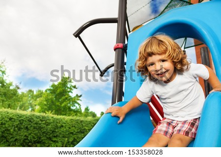 Close portrait of happy smiling little three years old boy about to slide on blue playground - stock photo