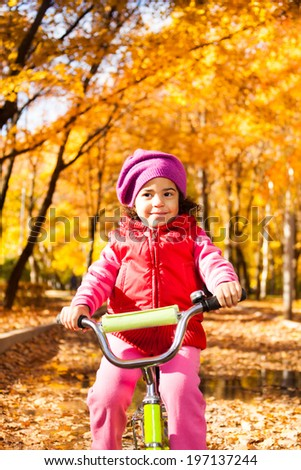 Close portrait of little black girl riding a bicycle in the park - stock photo