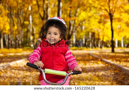 Close portrait of little black girl riding a bicycle in the park on the road covered with autumn oak and maple trees - stock photo