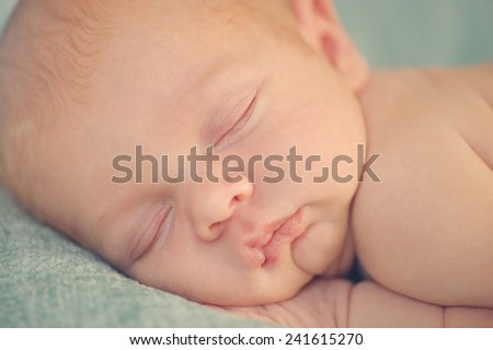 Close portrait of Newborn Baby Sleeping on Hands