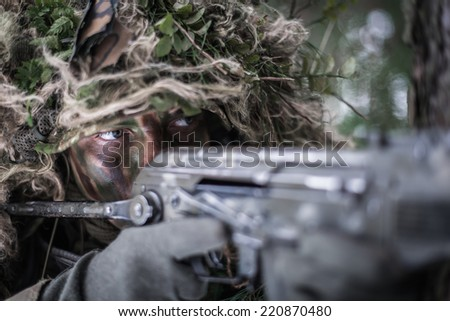 close portrait of special forces soldier dressed in ghillie suit, aiming with assault rifle - stock photo