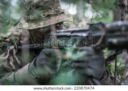 close portrait of special forces soldier wearing boonie hat, aiming with sub machine gun - stock photo