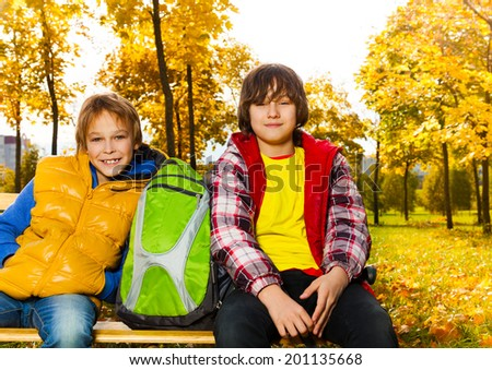 Close portrait of two happy boys sitting on the bench with backpack in autumn park - stock photo