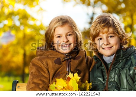 Close portrait of two smiling blond kids, boy and girl, twin siblings, with bouquet of leaves