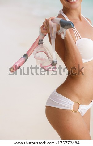 close portrait of Young woman with wet skin and with a snorkeling equipment on sand and going to swim in clear ocean - stock photo