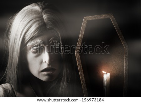 Close portrait on the face of a creepy vampire woman holding candle light in misty ghost forest - stock photo