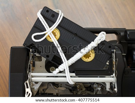 Close-roll video cassette vhs bound with rope, which is stuffed inside the mechanism of the camcorder. - stock photo