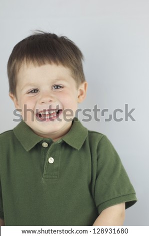 Close shot of a happy boy laughing and off to the left. - stock photo