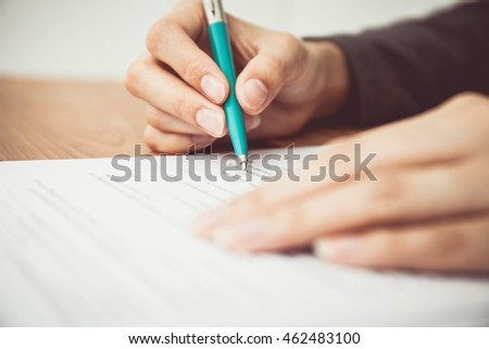 Close shot of a human hand writing contract