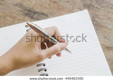 Close shot of a human hand writing something on the paper