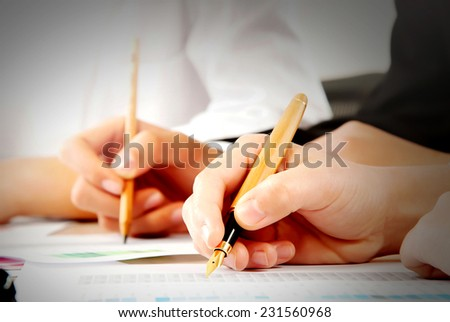 Close shot of a human hand writing something on the paper on the foreground - stock photo