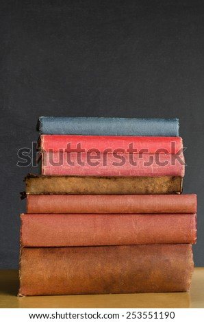Close shot of a pile of old, shabby, well used text books stacked in a pile on a desk in front of a black chalkboard.  Copy space above. - stock photo