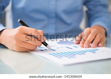 Close-shot of male hands holding a ballpoint and analyzing the financial diagram