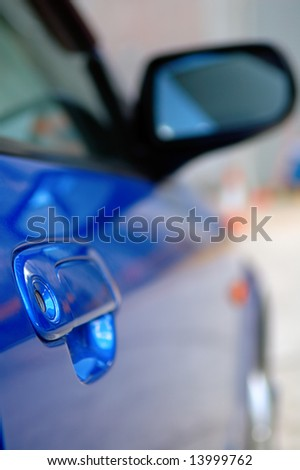 Close shot of right side mirror of shiny blue car - stock photo