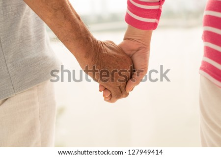 Close-shot of seniors holding hands expressing love and support - stock photo