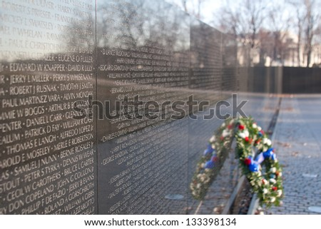 Close shot of the Vietnam Memorial, with a few names clearly seen, and a wreath sitting near by. - stock photo