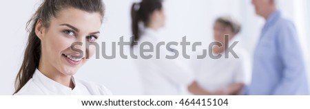 Close shot of young woman nurse's face with the woman doctor and elder couple at the nursery house at the background