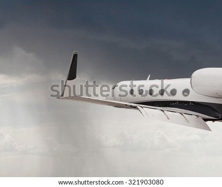 Close side view of a private jet flying - stock photo