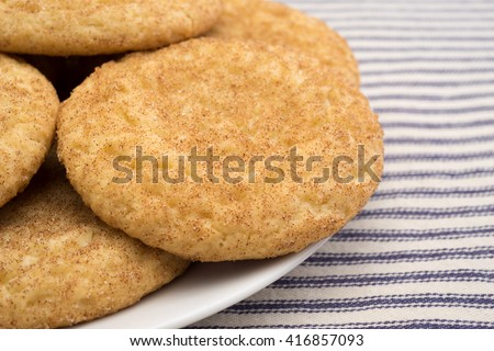 Close side view of freshly baked snickerdoodle cookies on an off white plate atop a blue striped tablecloth.