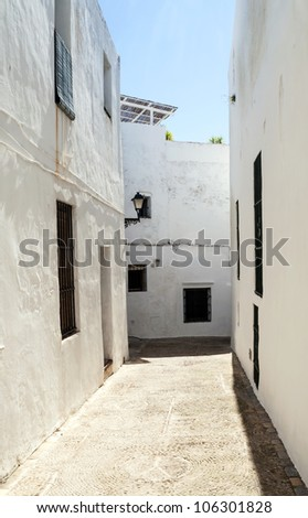 Close street decorated with white houses and bars in their windows It is Situated in a village in Spain - stock photo