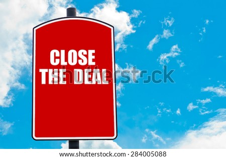 Close The Deal motivational quote written on red road sign isolated over clear blue sky background. Concept  image with available copy space