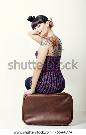 Close-uo portrait of a beautiful woman with a vintage style sitting on a bag
