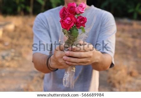 Close up a beautiful bouquet of red roses is given by young man. Romantic love or Valentine's day concept.